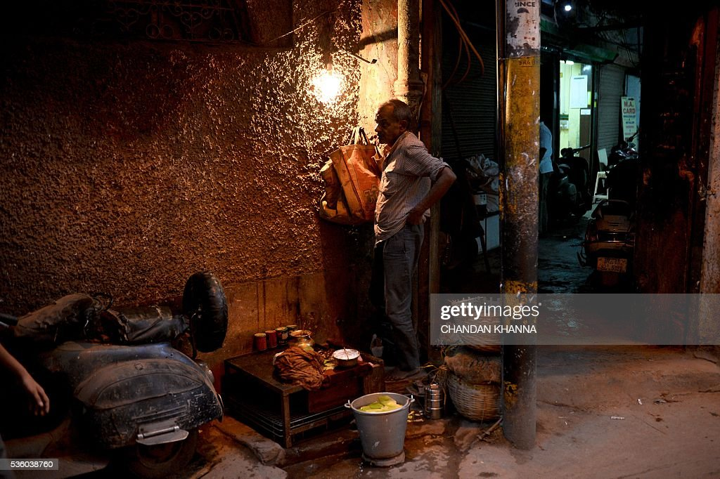 An Indian vendor who sells betel-nut mouth freshener waits for customers at his makeshift shop in the old quarters of New Delhi on May 31, 2016. / AFP / CHANDAN