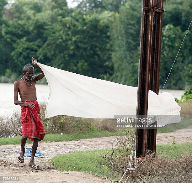 An Indian villager dries up his 'Dhoti' after getting wet when crossing through floodwaters to reach the village of Mabby in Darbhanga District some...
