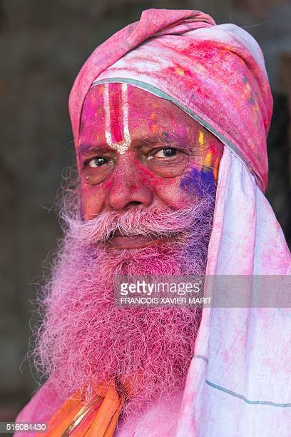 An Indian villager is smeared with colour powder during the Lathmar Holi festival at the Radha Rani temple in Barsana some 130kms from New Delhi on...