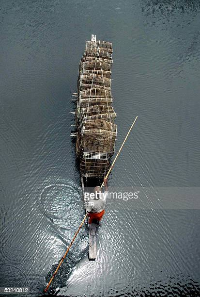 An Indian villager paddles his boat laden with fishing traps through floodwaters near the village of Dolybari on the outskirts of Guwahati 15 July...