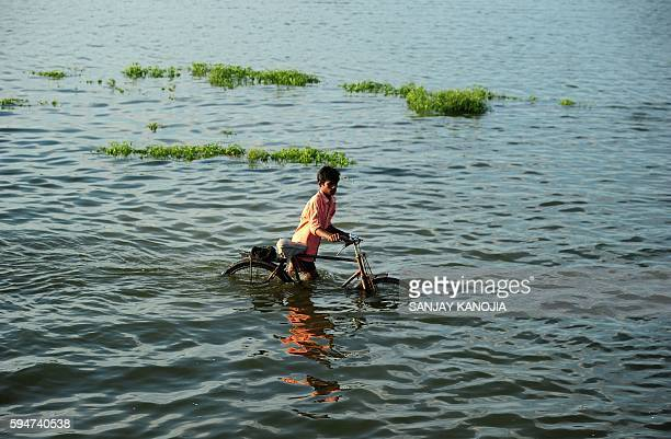 TOPSHOT An Indian villager pushes a bicycle as he crosses a flooded road at Naraha on the outskirts of Allahabad on August 24 2016 / AFP / SANJAY...