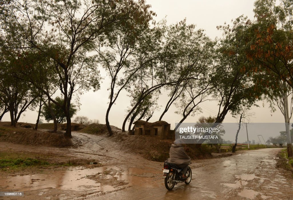 An Indian villager rides a scooter near a civilian bunker during a rain shower along the India-Pakistan border in Suchit-Garh, 36 kms southwest of Jammu on January 18, 2013. On both sides of the de facto border in Kashmir, villagers living on one of the world's most dangerous flashpoints have special reason to fear the return of tension between India and Pakistan. AFP PHOTO/Tauseef MUSTAFA