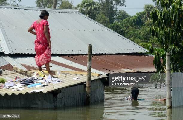 An Indian villager stands atop her partially submerged house at Alal village in Malda district in the Indian state of West Bengal on August 23 2017...