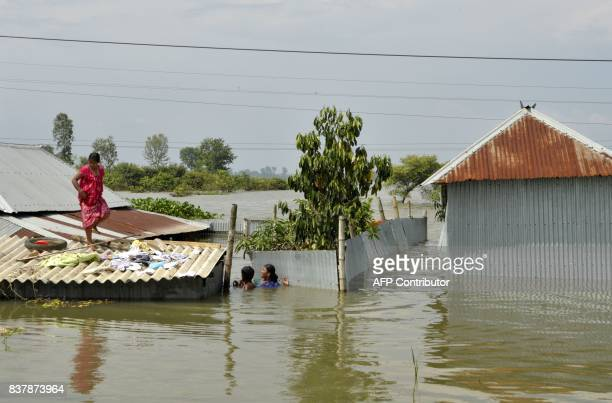 TOPSHOT An Indian villager stands atop her partially submerged house at Alal village in Malda district in the Indian state of West Bengal on August...