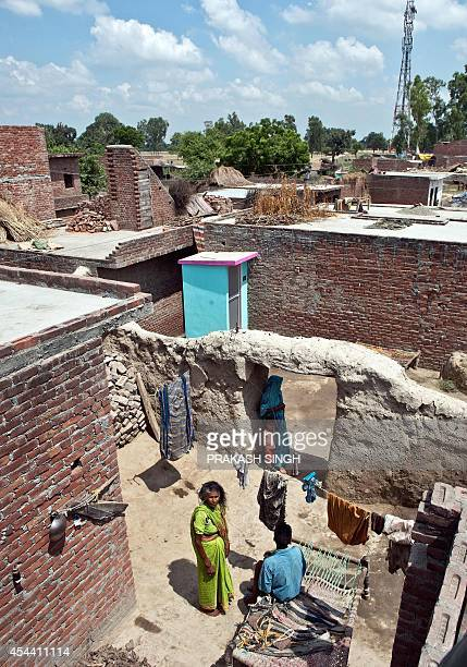 An Indian villager talks with his mother in their compound beside a newly built toilet by NGO Sulabh International with during the inauguration of...