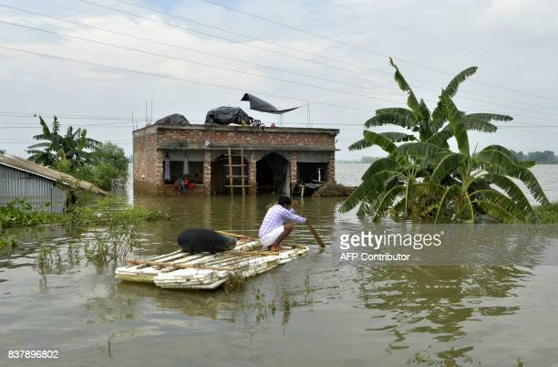 An Indian villager uses a banana raft outside his partially flooded house at Chachol village in Malda district in the Indian state of West Bengal on...