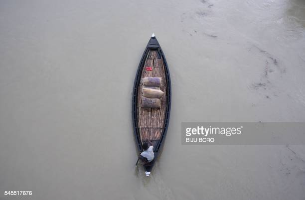 TOPSHOT An Indian villager uses a boat to transport rice through the floodaffected Murkata village in the Morigoan district of Assam on July 8 2016...