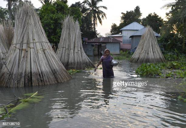 An Indian villager wades through flood waters to collect relief food near the submerged houses in Gazole village at Malda district in the Indian...