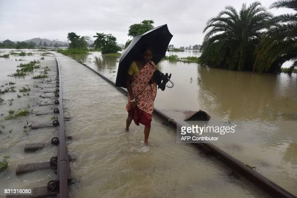 TOPSHOT An Indian villager walks along a submerged railway track in the floodaffected Jakhalabandha area in Koliabor some 186km from Guwahati the...