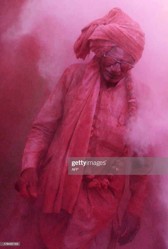 An Indian villager walks through clouds of coloured powder thrown by others during Lathmar Holi celebrations in the village of Jaab in Kosi Kalan on March 18, 2014. Holi, also called the Festival of Colours, is a popular Hindu spring festival observed in India at the end of the winter season on the last full moon day of the lunar month. AFP PHOTO/Chandan KHANNA