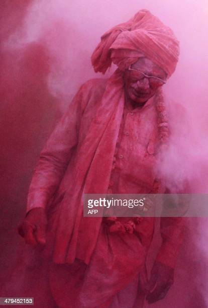An Indian villager walks through clouds of coloured powder thrown by others during Lathmar Holi celebrations in the village of Jaab in Kosi Kalan on...