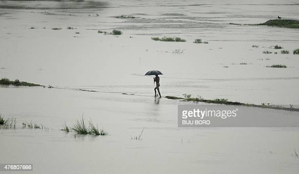 An Indian villager walks through the flood water at the flood affected Buraburi village some 60 kms from Guwahati the capital city of the...