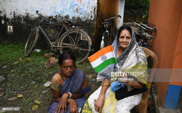 An Indian villager waves the national flag during Independence Day celebrations in Majhdia village of Nadia district east of Krishnanagar in West...