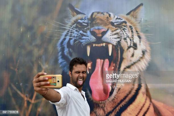 TOPSHOT An Indian visitor poses for a photograph in front of a picture of a tiger displayed on the last day of the 'Bharat Parav' festival at the...