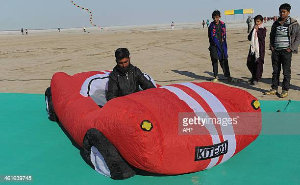 An Indian visitor sits in a carshaped kite belonging to unseen team members from the Estonian kiteflying team during the International Kite Festival...