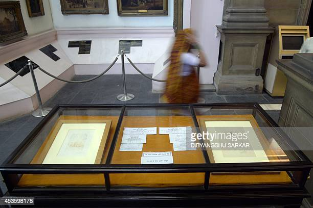 An Indian visitor walks past displays of two artworks by Salvador Dali in Durbar Hall of The Victoria Memorial in Kolkata on August 14 2014 The two...