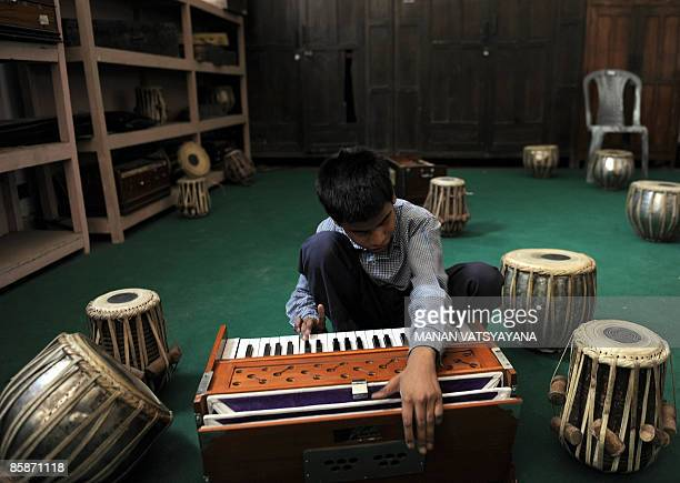 An Indian visually challenged student plays a harmonium at a school run by the Blind Relief Association in New Delhi on April 9 2009 The Blind Relief...