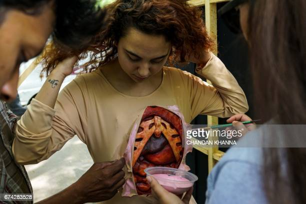 An Indian volunteer for animal rights group People for the Ethical Treatment of Animal gets dressed to wear a costume to show internal organs to...