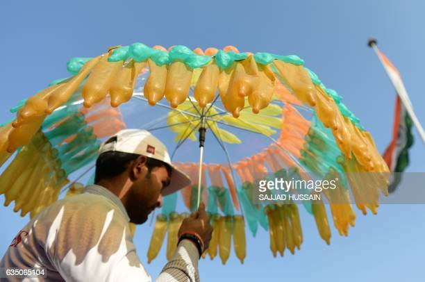 An Indian volunteer holds an umbrella decorated with condoms during an event to mark International Condom Day in New Delhi on February 13 2017 The...