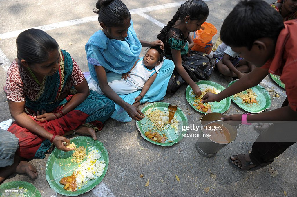 An Indian volunteer serves food to homeless people at a feeding programme for the poor in Hyderabad on March 17, 2013. India still has the worlds largest number of impoverished in a single country, of its nearly one billion inhabitants, an estimated 350-400 million live below the poverty line with 75 percent of them in the rural areas. AFP PHOTO / Noah SEELAM