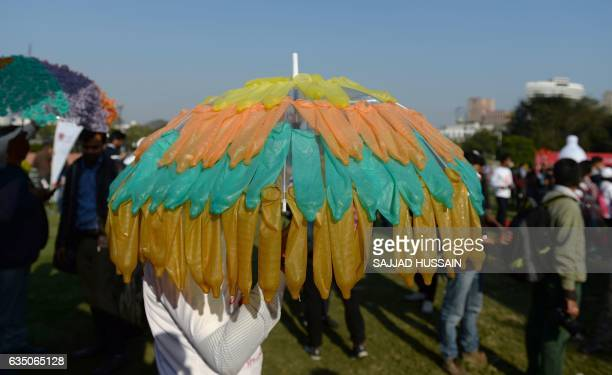 An Indian volunter holds an umbrella decorated with condoms during an event to mark International Condom Day in New Delhi on February 13 2017 The...