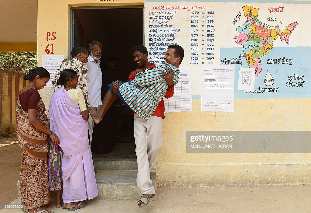 An Indian voter is helped out of a polling booth after he cast his ballot during state Assembly elections in Bangalore on May 5, 2013. Polling began this morning for the Assembly polls in Karnataka state in which the Indian Congress Party has pulled out all the stops to return to power in a complex battle after more than an eight year long gap. AFP PHOTO/ Manjunath KIRAN