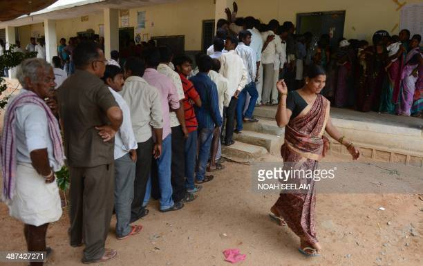 An Indian voter leaves after casting her ballot as others queue at a polling station at Rangareddy on the outskirts of Hyderabad on April 30 2014...