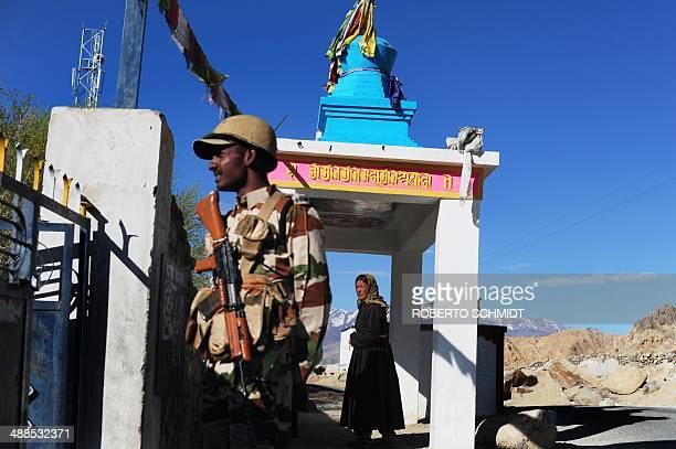 An Indian voter stands under a buddhist shrine after cast their ballot at a small rural school in Shushot Yongma a small enclave on the Indus river...