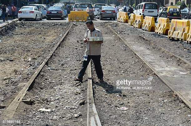 An Indian waiter carries empty tea glasses over old tram tracks discovered under an existing road in Mumbai on February 22 2016 The tracks were found...