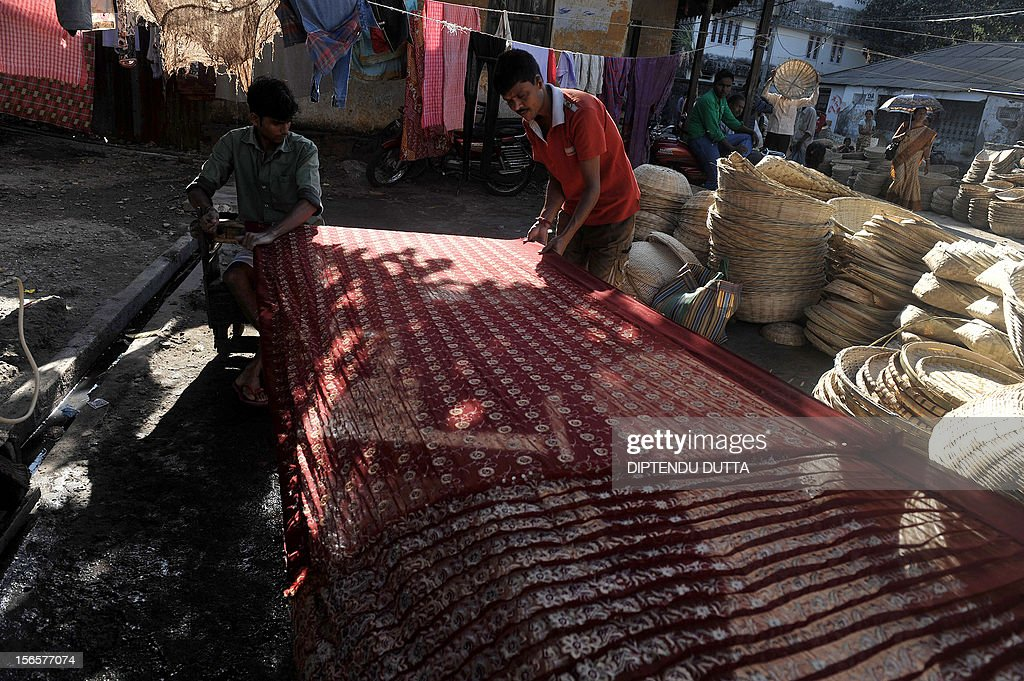 An Indian washerman works on a saree for dry cleaning at his home in Siliguri on November 17, 2012. Widening income gaps and rising numbers of unskilled young people could derail India's economic growth, speakers at a high-profile economic conference warned on November 8. AFP PHOTO/Diptendu DUTTA