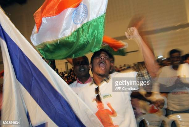 An Indian waves an Indian flag while another waves an Israeli flag as attendees celebrate while listening to a speech given by Prime Minister...