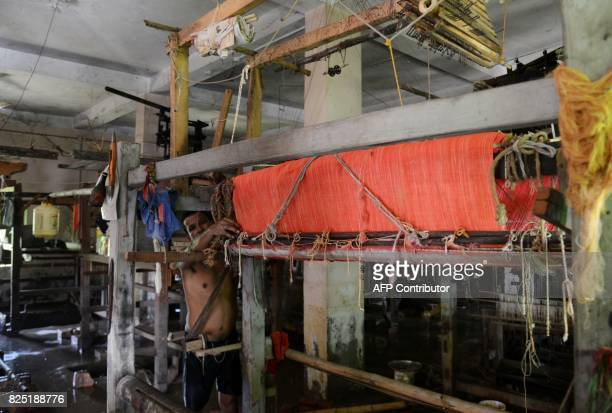 An Indian weaver affected by flooding checks handlooms as they clear floodwater from a workshop in Udaynarayanpur some 83kms west of Kolkata on...