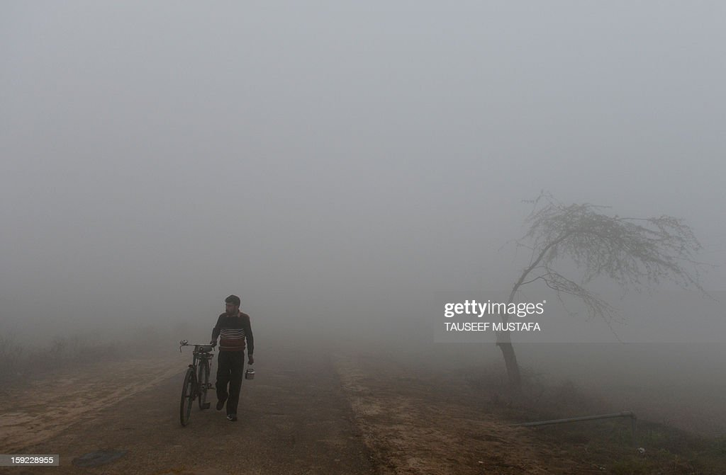 An Indian wheels his bicycle amid dense fog near the India-Pakistan border in Suchit-Garh, 36 kms southwest of Jammu, on January 10, 2013. The beheading of an Indian soldier may have sparked a war of words between Delhi and Islamabad but the two nuclear rivals are both determined to prevent it from wrecking a fragile peace process. Two Indian soldiers died after a firefight erupted in disputed Kashmir on Tuesday as a patrol moving in fog discovered Pakistani troops about 500 metres (yards) inside Indian territory, according to the Indian army. AFP PHOTO/Tauseef MUSTAFA