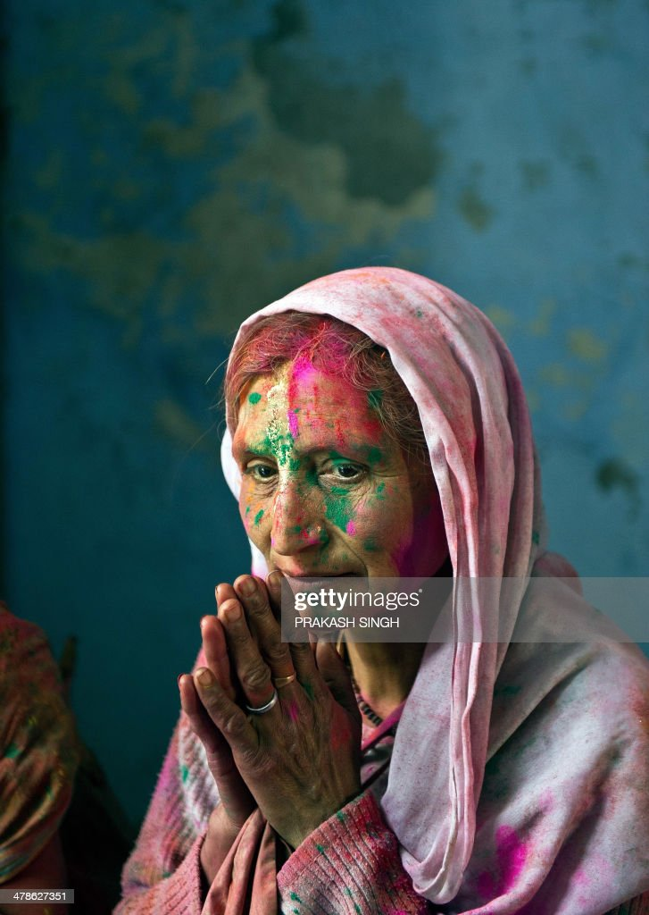 An Indian widow, seen smeared with coloured powder, rests after celebrating Holi in Vrindavan on March 14, 2014. Breaking centuries-old tradition, around 1,000 widows living in the holy city of Vrindavan celebrated the spring colour festival of Holi at Meera Sahabhagini Sadan in Vrindavan. In a symbolic gesture, the widows celebrated Holi with colours and gulal unlike the previous year where they only sprinkled flower petals over each other. As per Indian tradition, widows are considered social outcasts and refrain from celebrating Holi. AFP PHOTO/Prakash SINGH