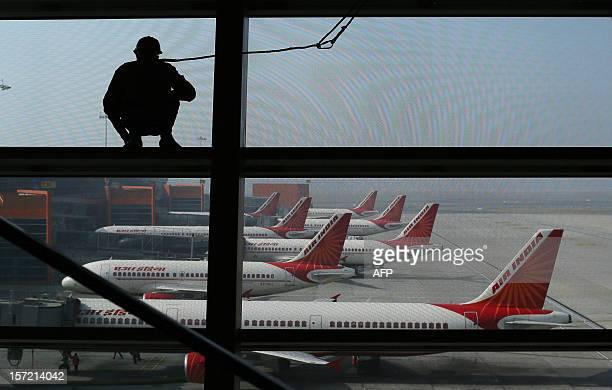 An Indian window cleaner stands on a beam overlooking Air India aircraft as they stand on the tarmac at Indira Gandhi International Airport in New...