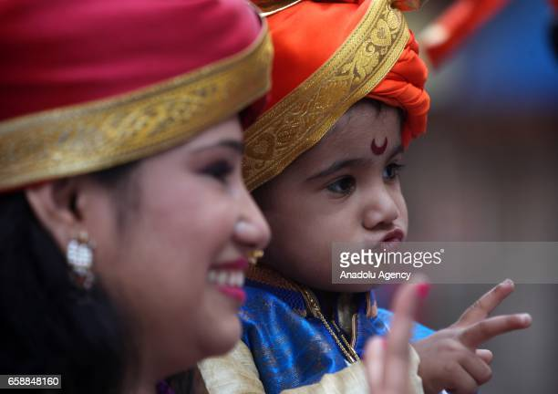 An Indian woman and a boy wear traditional dresses celebrate the Gudi Padwa Maharashtrian's New Year in Mumbai India on March 28 2017 Gudi Padwa is...