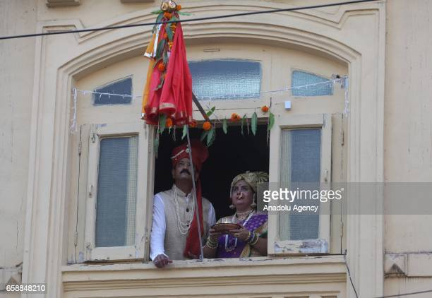 An Indian woman and a man wear traditional clothes put a stick with a traditional cloth outward of the window to celebrate the Gudi Padwa...