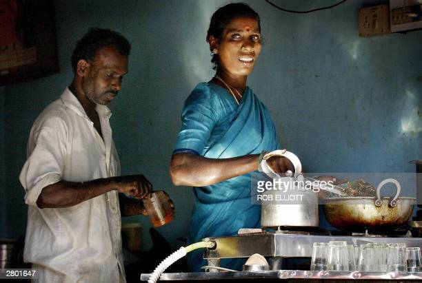 An Indian woman and man prepare food for sale at a small outlet in the streets of Bombay 11 December 2003 Bombay street food is famous throughout...