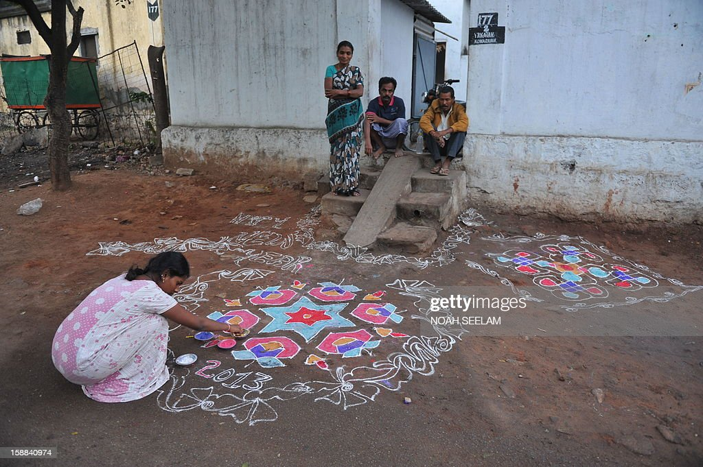 An Indian woman (L) applies coloured powder to her 'rangoli', a Hindu ritual design, in front of her house in Hyderabad on January 1, 2013. Rangolis are drawn in front of homes early in the morning with a beautiful motif to welcome relatives and friends to mark the New Year. AFP PHOTO / Noah SEELAM