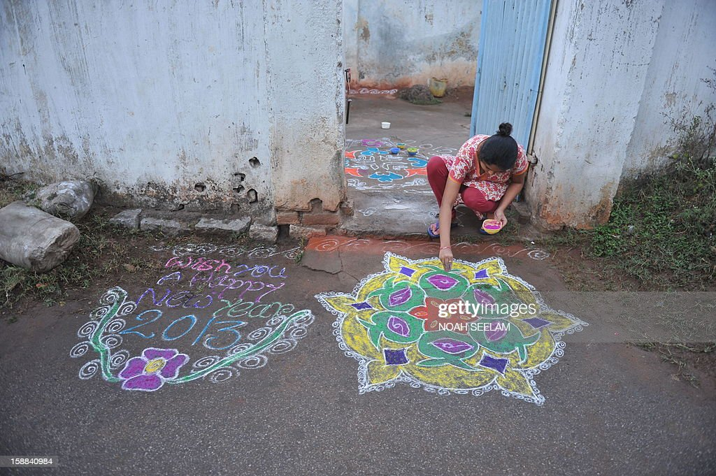 An Indian woman applies coloured powder to her 'rangoli', a Hindu ritual design, in front of her house in Hyderabad on January 1, 2013. Rangolis are drawn in front of homes early in the morning with a beautiful motif to welcome relatives and friends to mark the New Year. AFP PHOTO / Noah SEELAM
