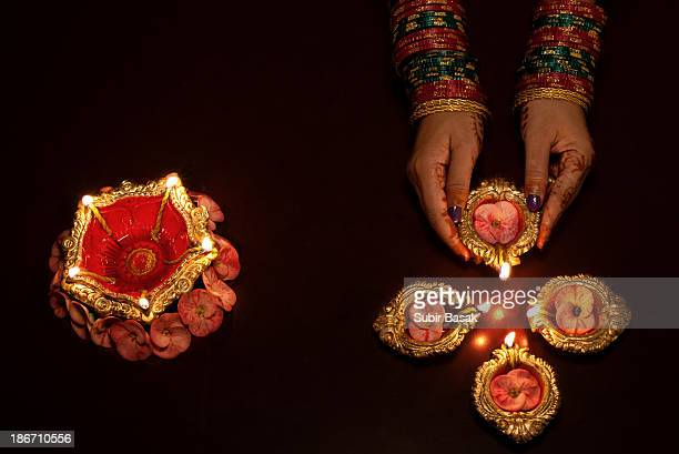 An Indian woman arranging  earthen lamps at diwali