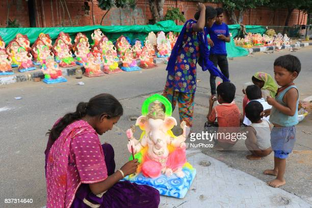 An Indian woman artist giving final touch to Idols of elephant headed Hindu god Ganesh ahead of Ganesh Chaturthi festival in Jaipur Rajasthan India...