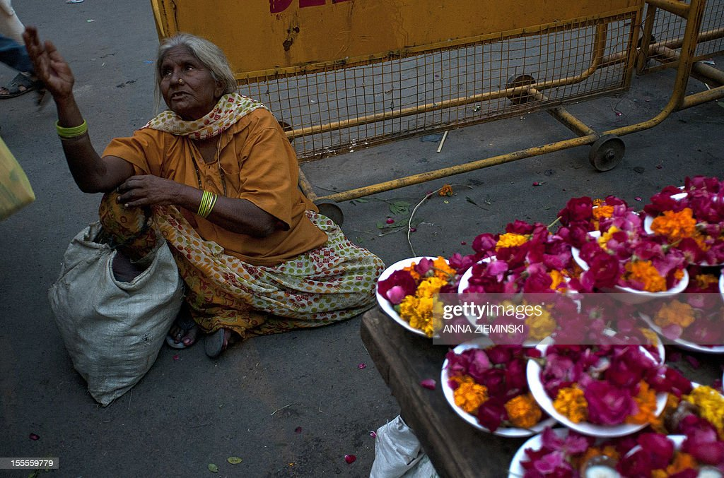 An Indian woman begs next to a flower-seller's stall outside a temple in New Delhi on November 5, 2012. The ruling Congress party has rolled out its big guns to defend the move to let the likes of Walmart set up shop in India, but they are confronting an alliance stretching across the political spectrum. Prime Minister Manmohan Singh's left-leaning government announced in September that it was lowering the bar for foreign firms to operate in sectors ranging from retail to insurance, in a bid to revive its fortunes before elections in 2014 but elsewhere in the country, a broad array of Congress opponents are vowing to scupper the changes. AFP PHOTO/Anna ZIEMINSKI
