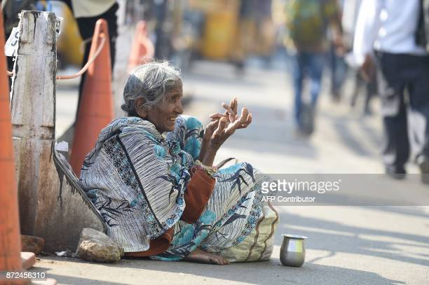 An Indian woman begs on the side of the road in Hyderabad on November 10 2017 A city in southern India has banned begging in public places ahead of a...