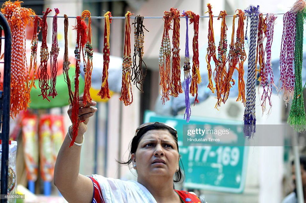 An Indian woman buys Rakhis ahead of Raksha Bandhan on August 7, 2014 in Noida, India. The festival of Raksha Bandhan' or 'Rakhi' celebrate the brother-sister love. Sisters tie sacred Rakhi string on their brothers' right wrists and pray for their protection.