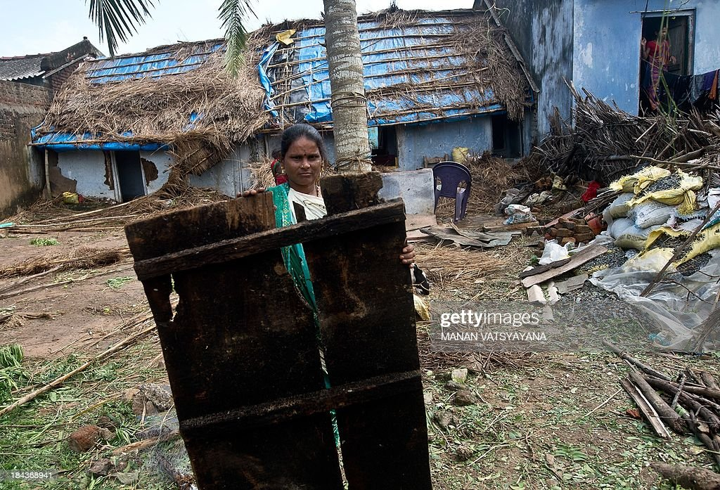 An Indian woman carries a broken door from her house in Gopalpur on October 13, 2013. Cyclone Phailin left a trail of destruction along India's east coast and up to seven people dead after the biggest evacuation in the country's history helped minimise casualties.