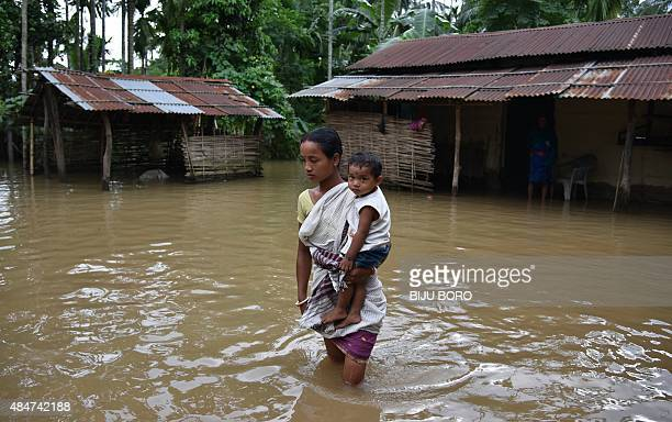 An Indian woman carries a child through flood waters in Singimari village in Bongaigoan district some 160 km from Guwahati in the northeastern state...