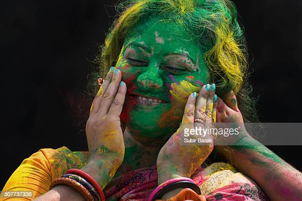 An Indian woman celebrating holi festival with color powder.