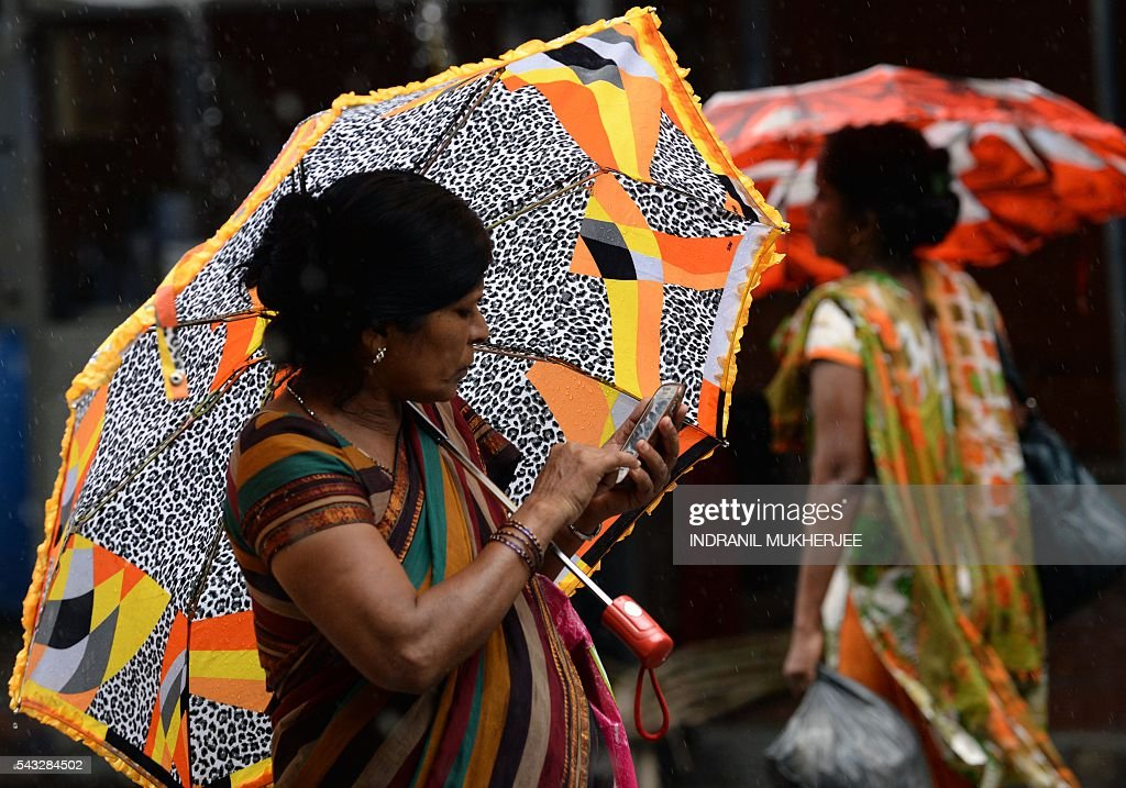 An Indian woman checks her mobile phone while walking through a business district in Mumbai on June 27, 2016. India is the world's second-largest mobile phone market by users after China. / AFP / INDRANIL
