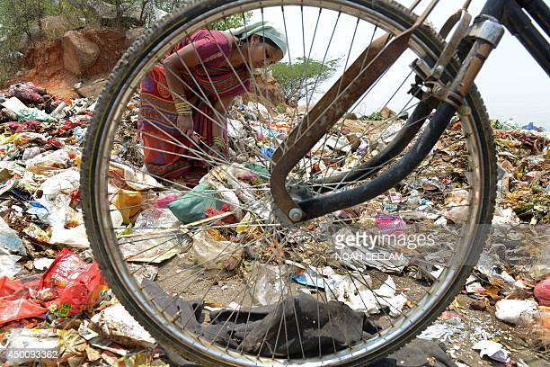An Indian woman collects recyclable items at a garbage dump yard in Hyderabad on June 5 2014 on World Environment Day India's cities are becoming...